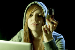 Young attractive teen woman wearing hood on hacking laptop computer cybercrime cyber crime concept. Young attractive teen woman wearing hood on looking dark and stock image