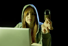 Young attractive teen woman wearing hood on hacking laptop computer cybercrime cyber crime concept. Young attractive teen woman wearing hood on looking dark and stock images