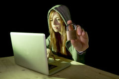 Young attractive teen woman wearing hood on hacking laptop computer cybercrime cyber crime concept Royalty Free Stock Images