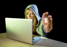 Young attractive teen woman wearing hoodie hacking laptop cybercrime cyber crime concept. Young attractive teen woman wearing hood on looking dark and dangerous stock photos