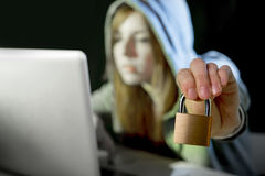 Young attractive teen woman wearing hoodie hacking laptop cybercrime cyber crime concept. Young attractive teen woman wearing hood on looking dark and dangerous royalty free stock image