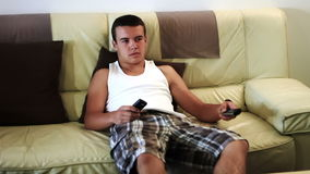 Young attractive teenager boy  watching television on sofa stock video