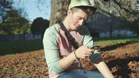 Young attractive teenager with a smart phone in autumn park. stock video
