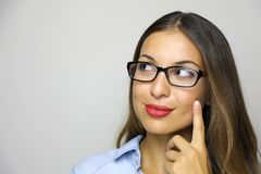 Young attractive thinking woman looking to the side with finger. On cheek and glasses over white background. Copy space royalty free stock photos
