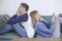 Young attractive and tired internet addict couple using app on mobile phone ignoring each other sitting back to back at home livin. G room sofa couch in slaves royalty free stock image