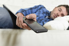 Young attractive tired and overworked falling asleep at home couch with mobile phone and digital tablet pad. In his hands in internet technology addiction and royalty free stock photography