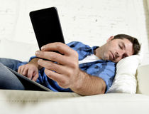 Young attractive tired and overworked falling asleep at home couch with mobile phone and digital tablet pad Royalty Free Stock Photos