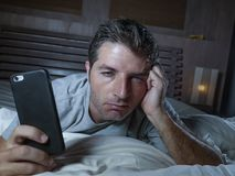 Young attractive tired and sleepy man using mobile phone at home lying on bed late at night falling asleep while networking or. Using social media in internet stock photos