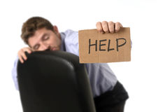 Young attractive tired and wasted businessman sitting on office chair asking for help in stress Stock Image