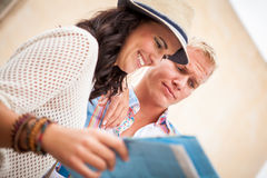 Young attractive tourist couple with city map in summer Royalty Free Stock Image