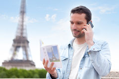 Young attractive tourist reading a guide of Paris Royalty Free Stock Images