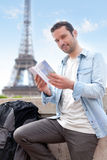Young attractive tourist reading a guide of Paris Royalty Free Stock Image