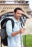 Young attractive tourist reading map in Paris Royalty Free Stock Image