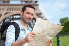 Young attractive tourist reading map in Paris Stock Photo
