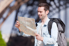 Young attractive tourist reading map in Paris Royalty Free Stock Images