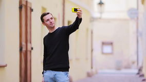 Young attractive tourist taking selfie photo with mobile phone outdoors enjoying holidays travel destination in tourism. Tourist man taking travel photos with stock video