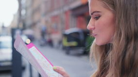 Young attractive tourist using map during sightseeing. Beautiful young caucasian woman using a map for orientation during sightseeing in a city stock video