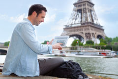 Young attractive tourist using tablet in Paris Royalty Free Stock Image