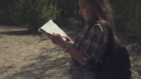 Young attractive tourist woman with backpack checking with her map and looking aroiund on local terrain. Camera is stock video footage
