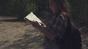 Young attractive tourist woman with backpack looking to her map and lifting up eyes checking with local terrain. Camera stock video footage