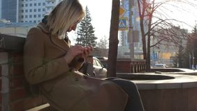 Young attractive trendy businesswoman using smartphone at city downtown. Young attractive trendy businesswoman using smartphone at city center street stock footage
