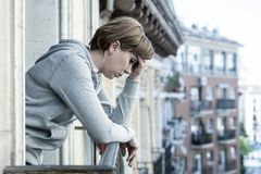 Young attractive unhappy depressed lonely woman looking down hopeless on the balcony at home. Having feelings of frustration, dissatisfaction, anxiety and Stock Image