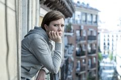 Young attractive unhappy lonely woman suffering from depression looking sad on the balcony at home. Young attractive, unhappy sad caucasian woman suffering from royalty free stock images