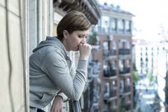 Young attractive unhappy lonely woman suffering from depression looking worried on the balcony at home. Young attractive, unhappy sad caucasian woman suffering stock photography