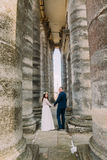 Young attractive wedding couple posing between rows of antique building stone columns Stock Image