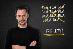 Young attractive white man with arm crossed with a `bla bla bla... Do it` text on a blackboard background royalty free stock image