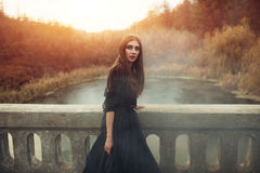 Young attractive Witch walking on the bridge in heavy black smoke. stock images