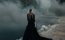 Young attractive Witch walking on the bridge in heavy black smoke. Young attractive Witch in black dress walking on the old bridge in heavy black smoke. Dark royalty free stock photography
