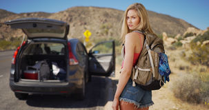 Young attractive woman abandons vehicle in the desert to steal a Royalty Free Stock Photography