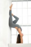 Young attractive woman in Adho Mukha Vrksasana pose, window back Stock Images