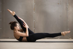 Young attractive woman in alternate leg stretch pose, grey studi. Young attractive woman doing alternate leg stretch, fitness exercise, working out, wearing Stock Photography