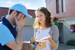 Young attractive woman angry against delivery man Royalty Free Stock Images