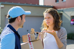Young attractive woman angry against delivery man Royalty Free Stock Image