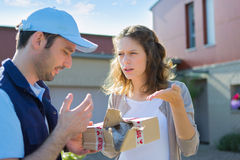 Young attractive woman angry against delivery man Stock Photo