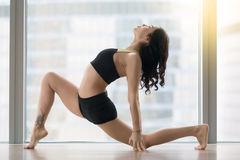 Young attractive woman in anjaneyasana pose against floor window Royalty Free Stock Image