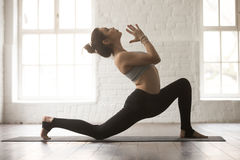Young attractive woman in anjaneyasana pose, white loft studio b Stock Photo