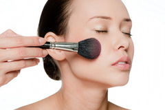 Young and attractive woman applying blusher Stock Photography