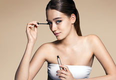 Young and attractive woman applying mascara Stock Photography