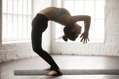 Young attractive woman in Ardha Chakrasana pose, white loft stud Royalty Free Stock Image