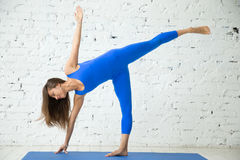 Young attractive woman in Ardha Chandrasana pose, white studio b Royalty Free Stock Photography