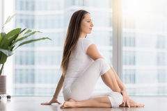 Young attractive woman in Ardha Matsyendrasana pose against floo Royalty Free Stock Photography