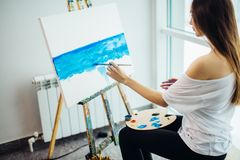 Attractive woman artist painting sea-scape in workshop stock photos