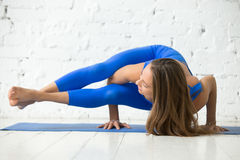 Young attractive woman in Astavakrasana pose, white studio backg. Young attractive happy woman practicing yoga, standing in Eight Angle exercise, Astavakrasana Royalty Free Stock Photo