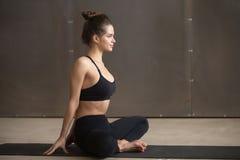 Young attractive woman in baddha konasana pose, grey studio back Stock Images