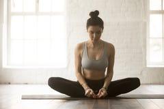 Young attractive woman in baddha konasana pose, white loft studi. Young attractive yogi woman practicing yoga concept, sitting in baddha konasana exercise Royalty Free Stock Images