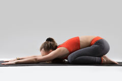 Young attractive woman in Balasana pose, grey studio background Royalty Free Stock Image